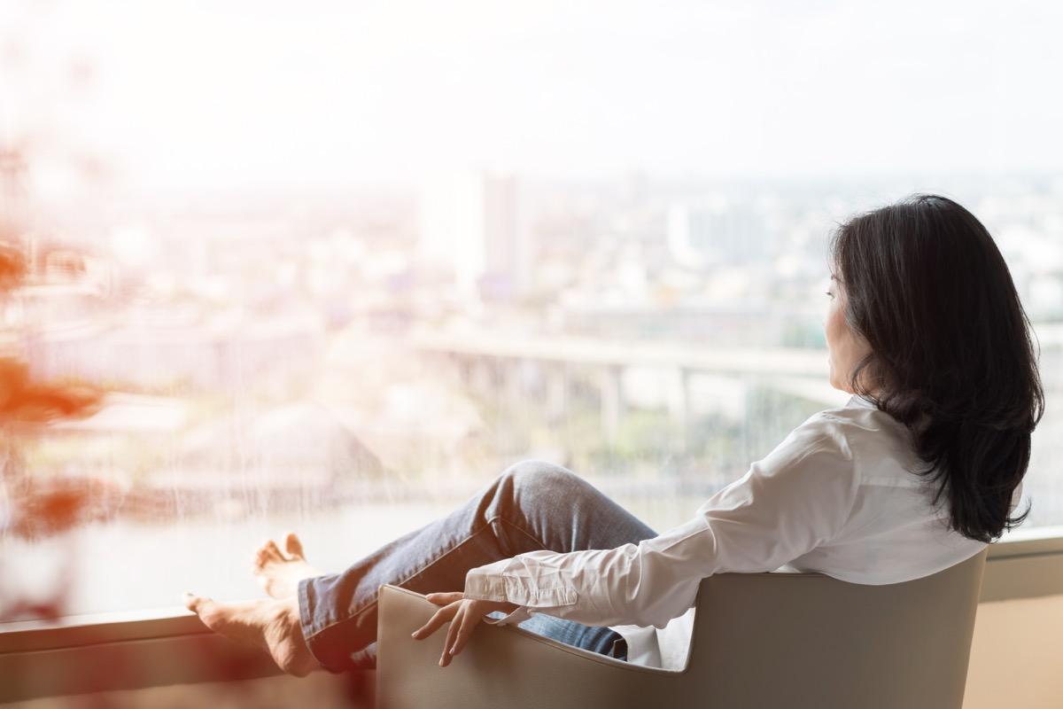 woman looking outside on balcony