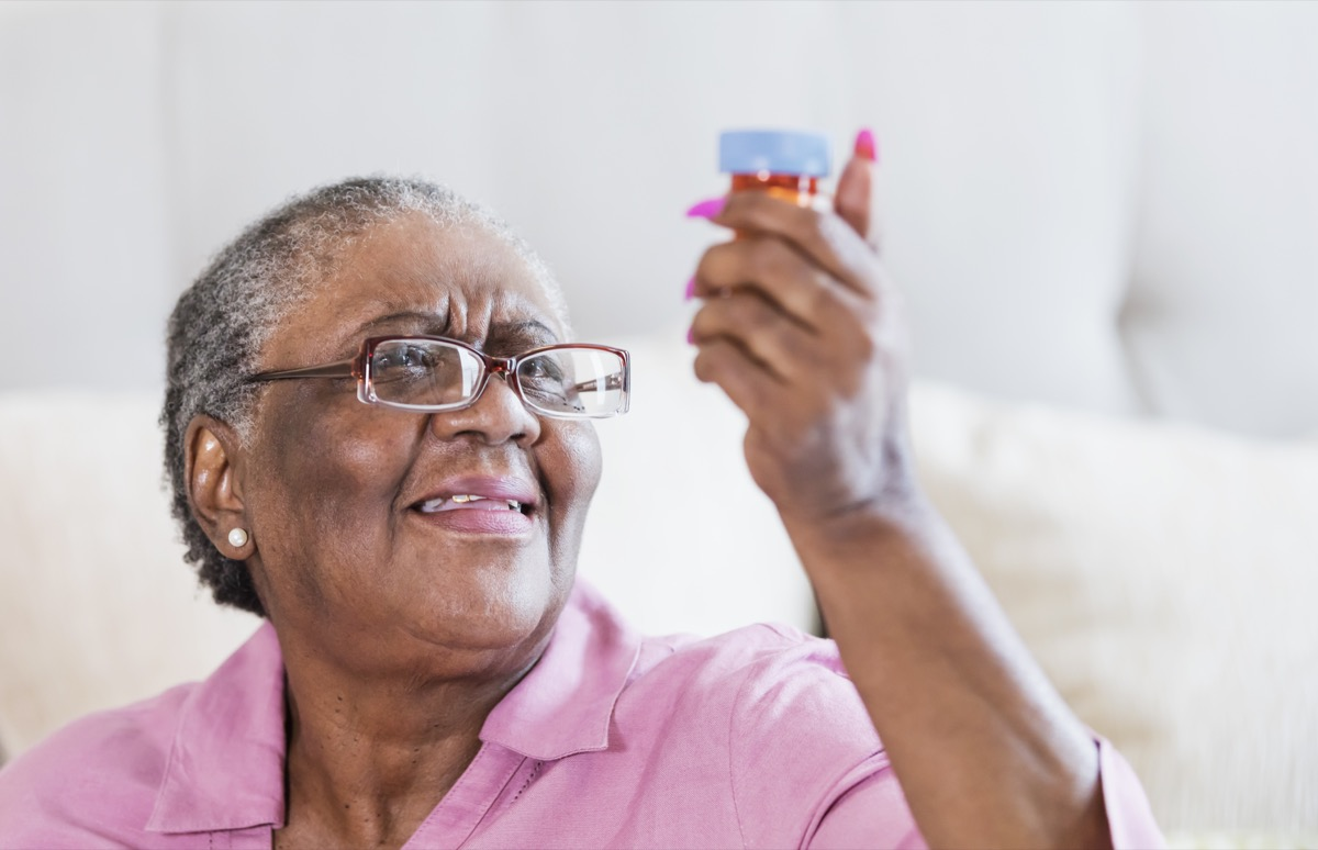 Senior African American woman struggling to read the label on a medicine