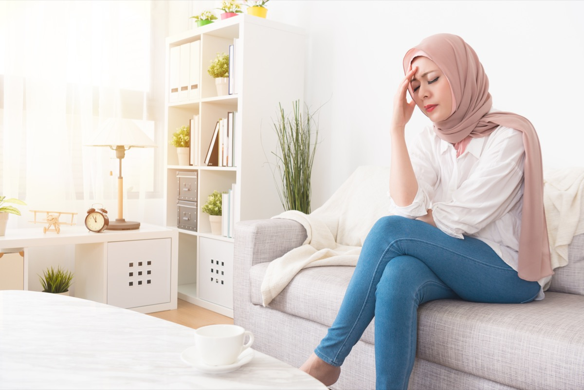 Woman sad and alone sitting on the couch