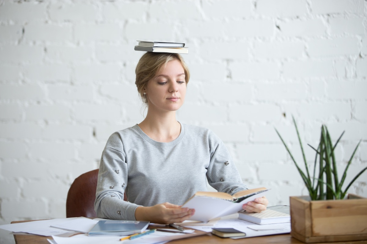 Portrait of attractive woman at desk, books on her head