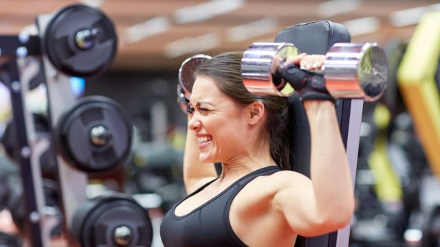 woman struggling to lift weights