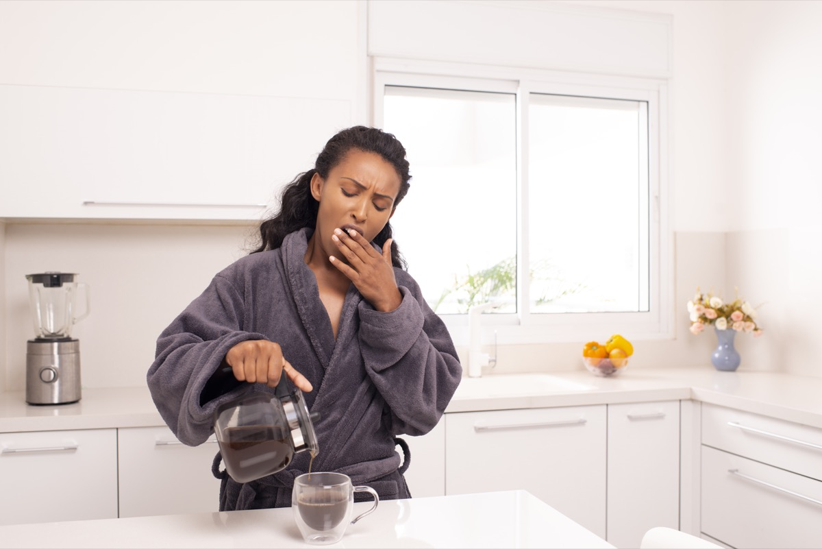 Woman yawning while she pours herself some coffee