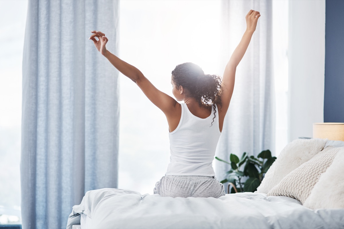 woman stretching after she wakes up in the morning