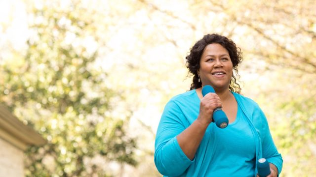 Older black woman walking and exercising with weights in her hands