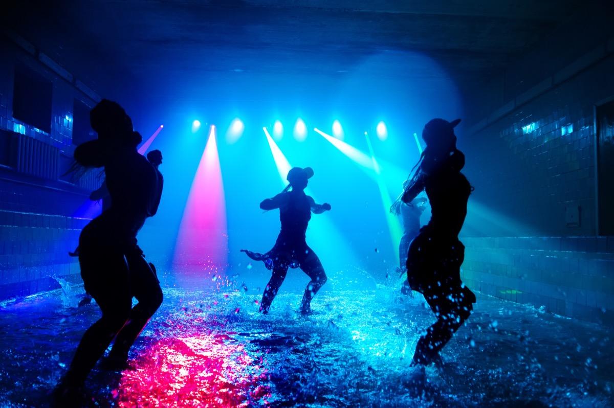 women dancing on dark stage