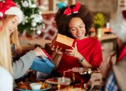 young black woman opening gifts sitting next to blonde friend holding box