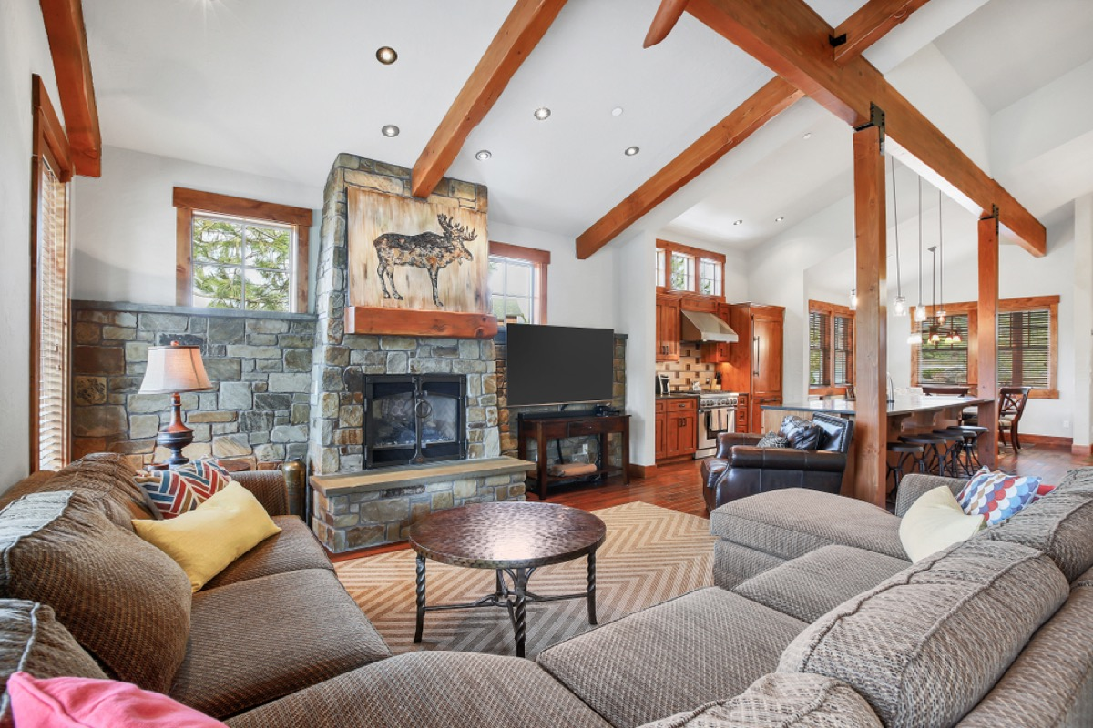 living room with gray couches and wood beamed ceiling