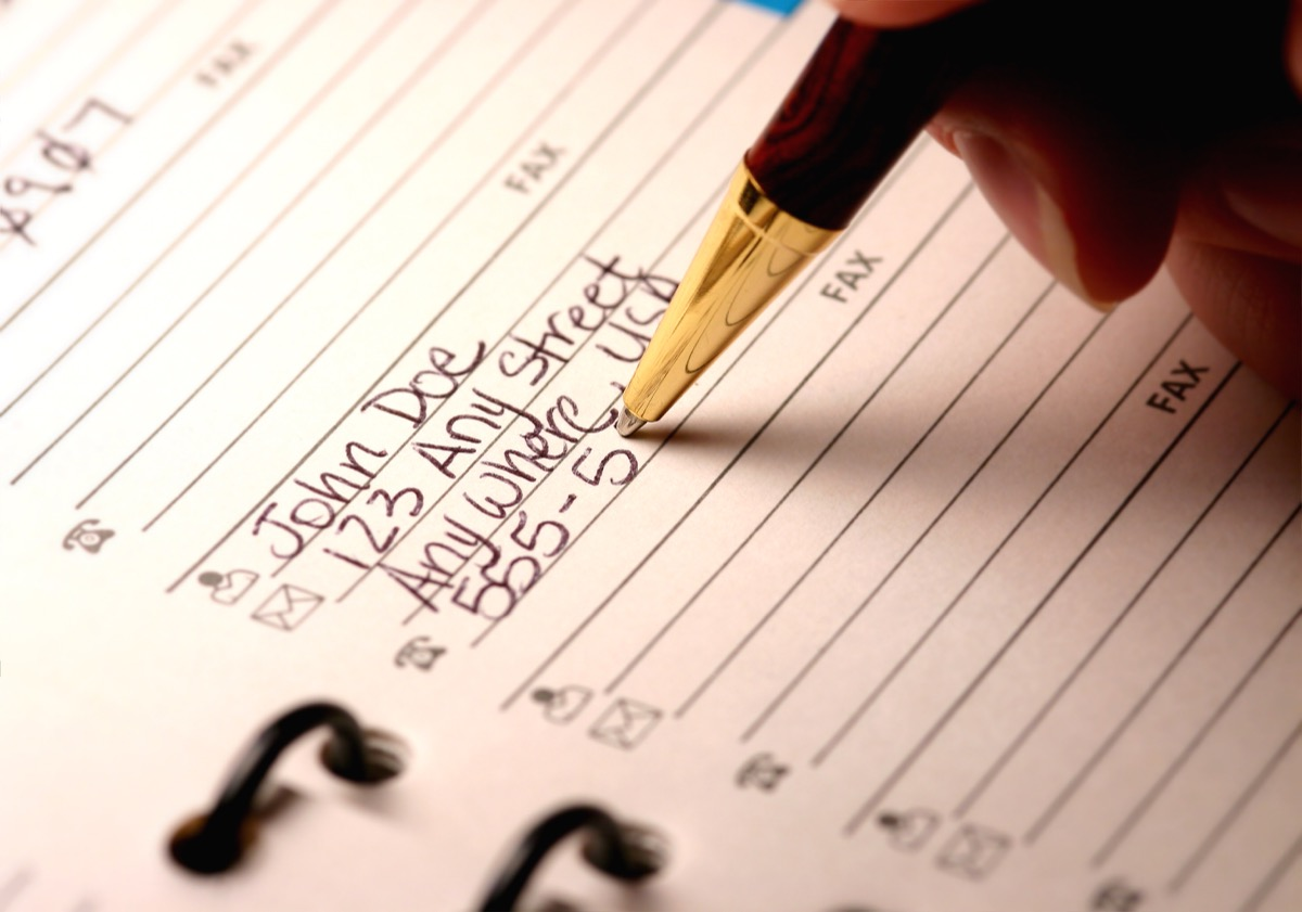 woman writing down important phone numbers in address book