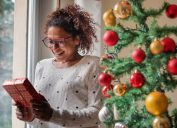young black woman holding gift in front of christmas tree