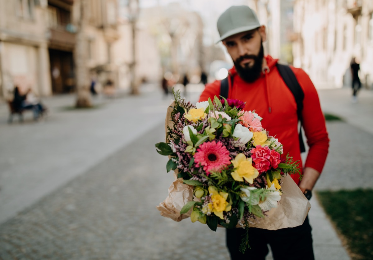 Young man carrying flower bouquet