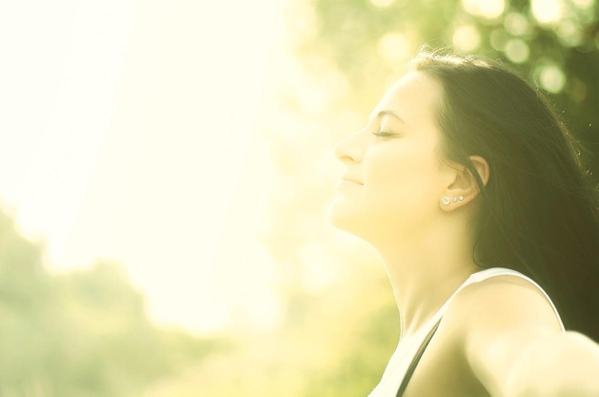 young woman enjoys sun beams at summer park.