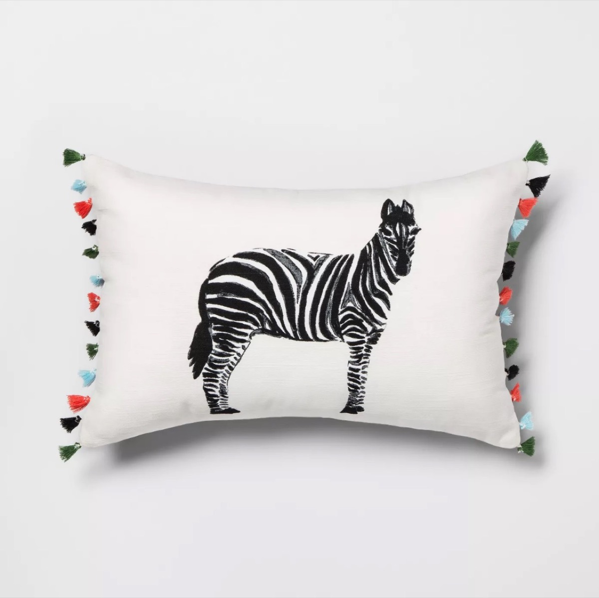 white throw pillow with zebra in the center and multicolored tassels