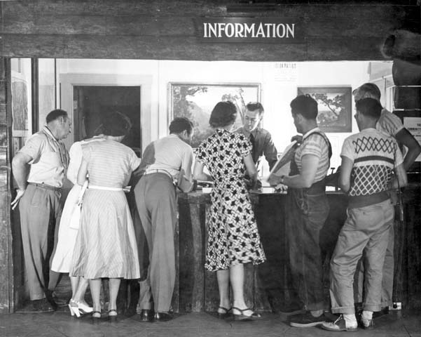 a line of people wait in front of an information booth