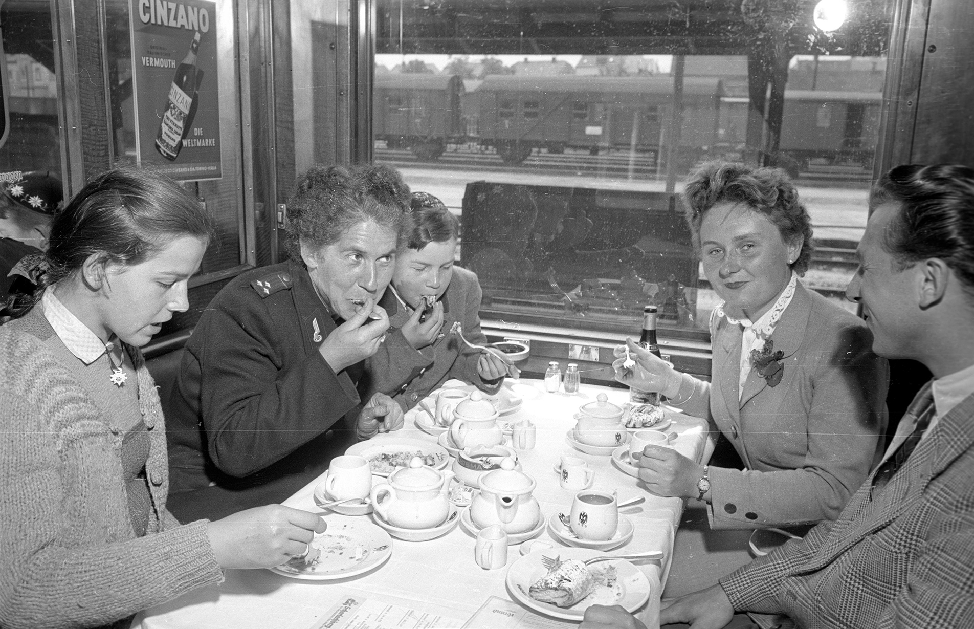 a group of friends eat dinner in a train car