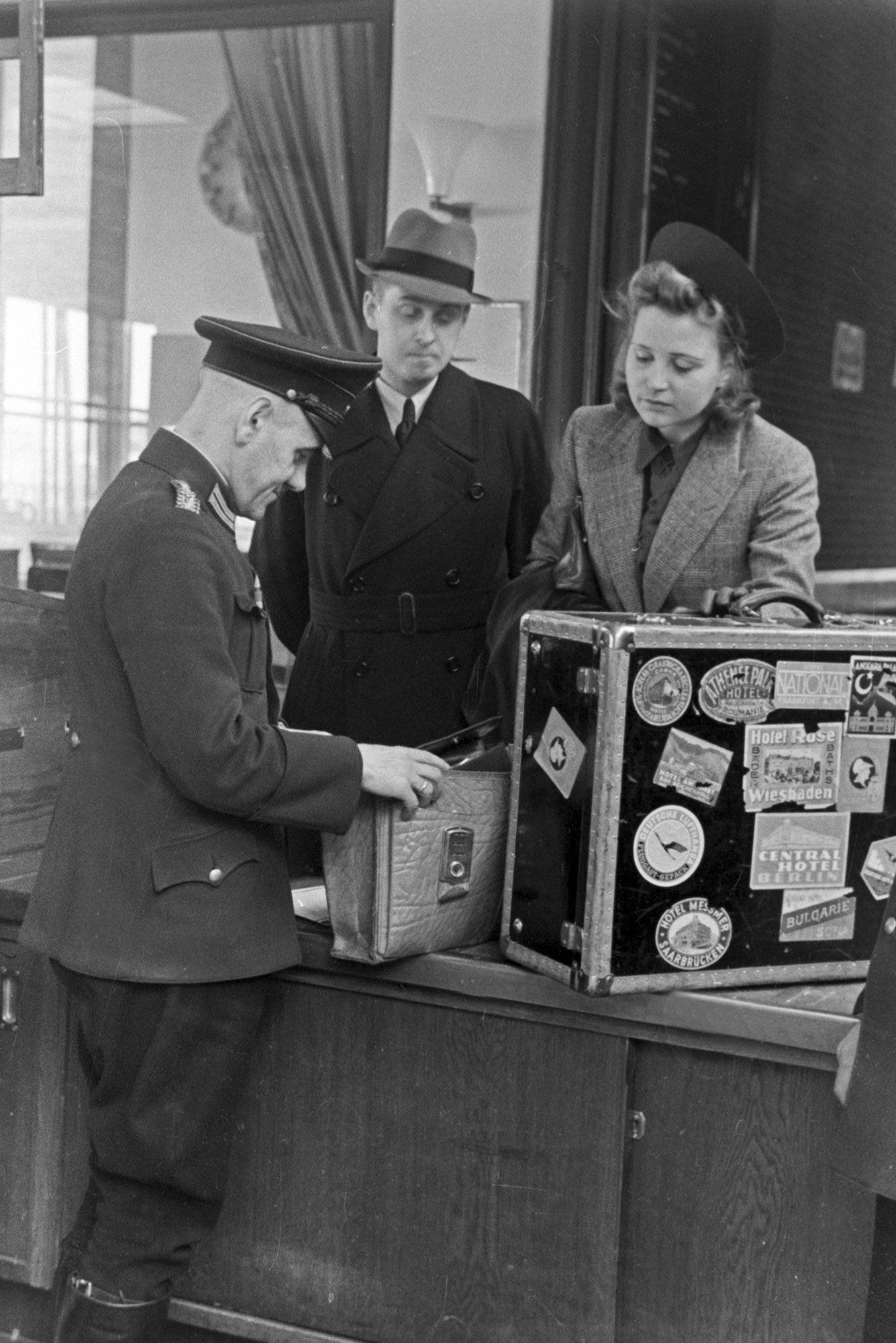 a man and woman watch as a customs officer goes through their suitcases