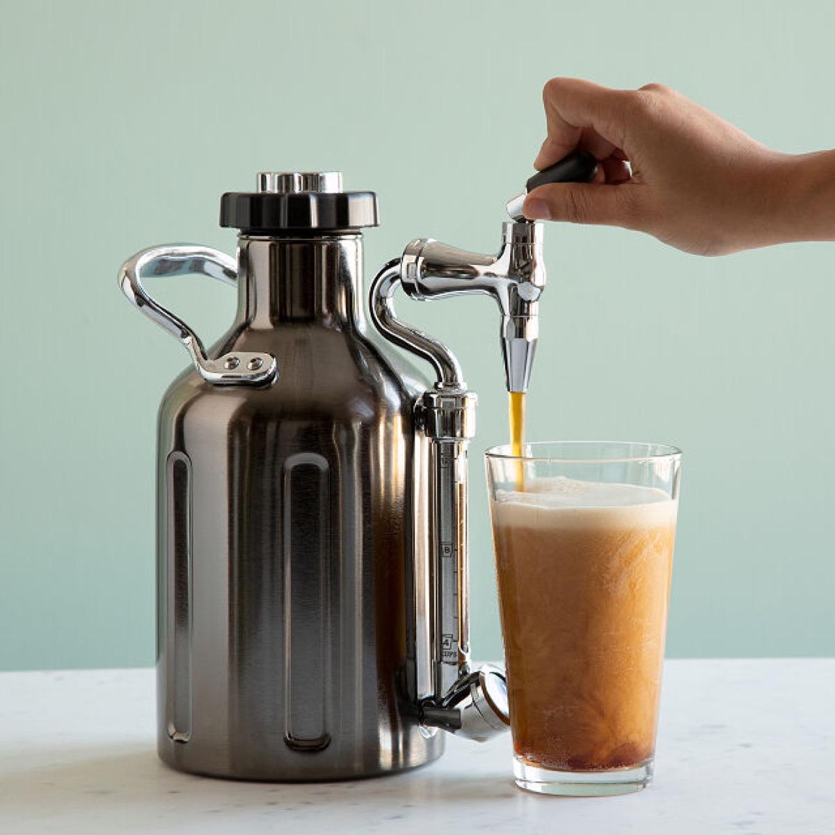 person pouring nitro cold brew into cup