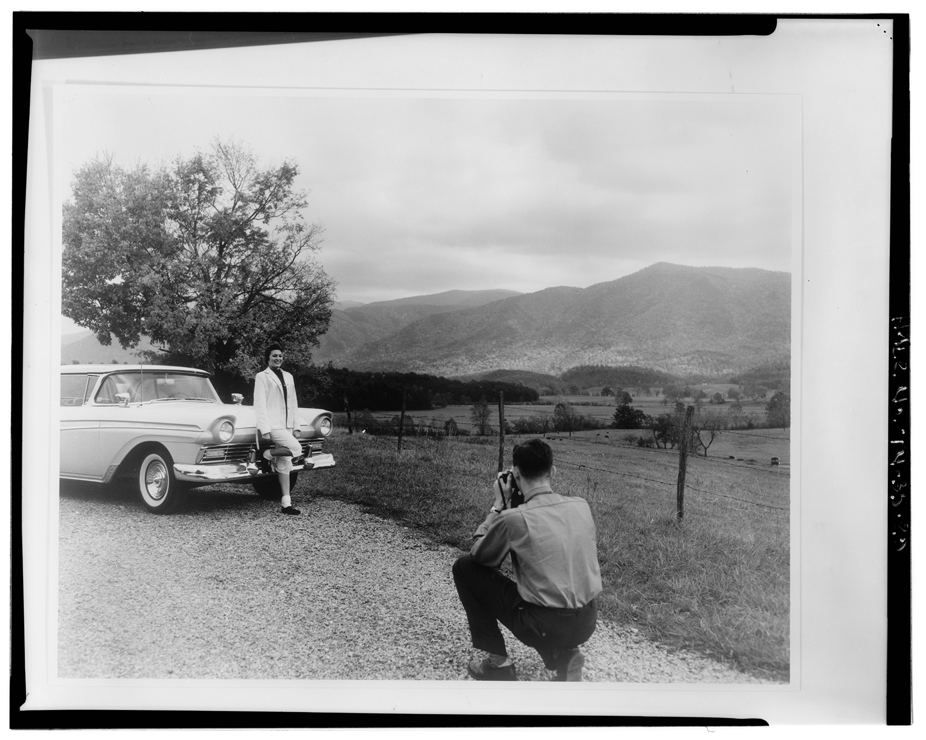 a man takes a photo of a girl leaning against a car