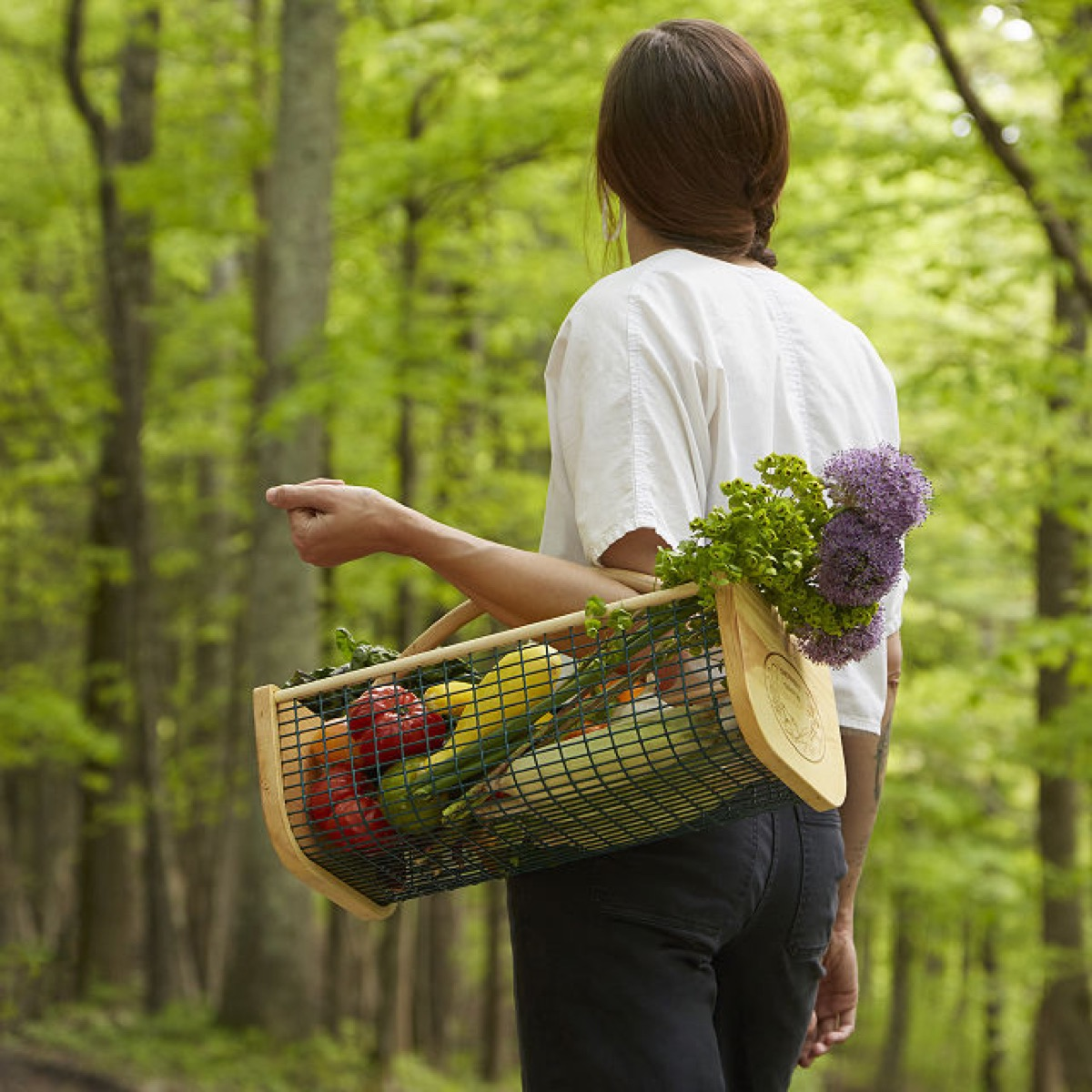 woman carrying veggies in harvest basket