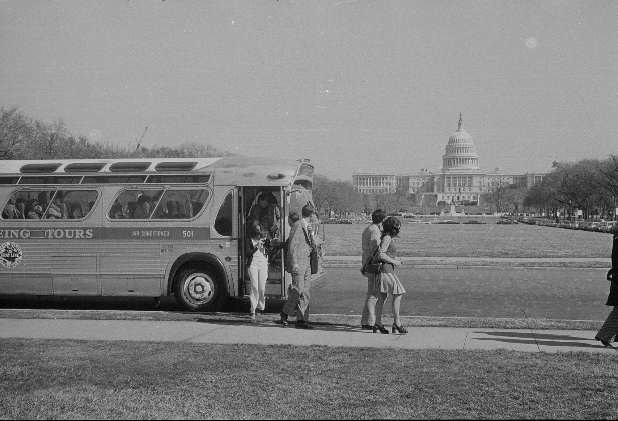 a group of people get off a bus in front of capitol hill