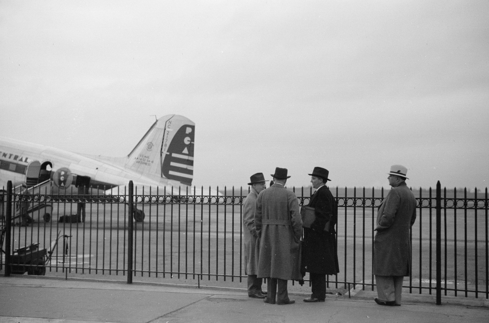 four men wait for a plane to land on the tarmac