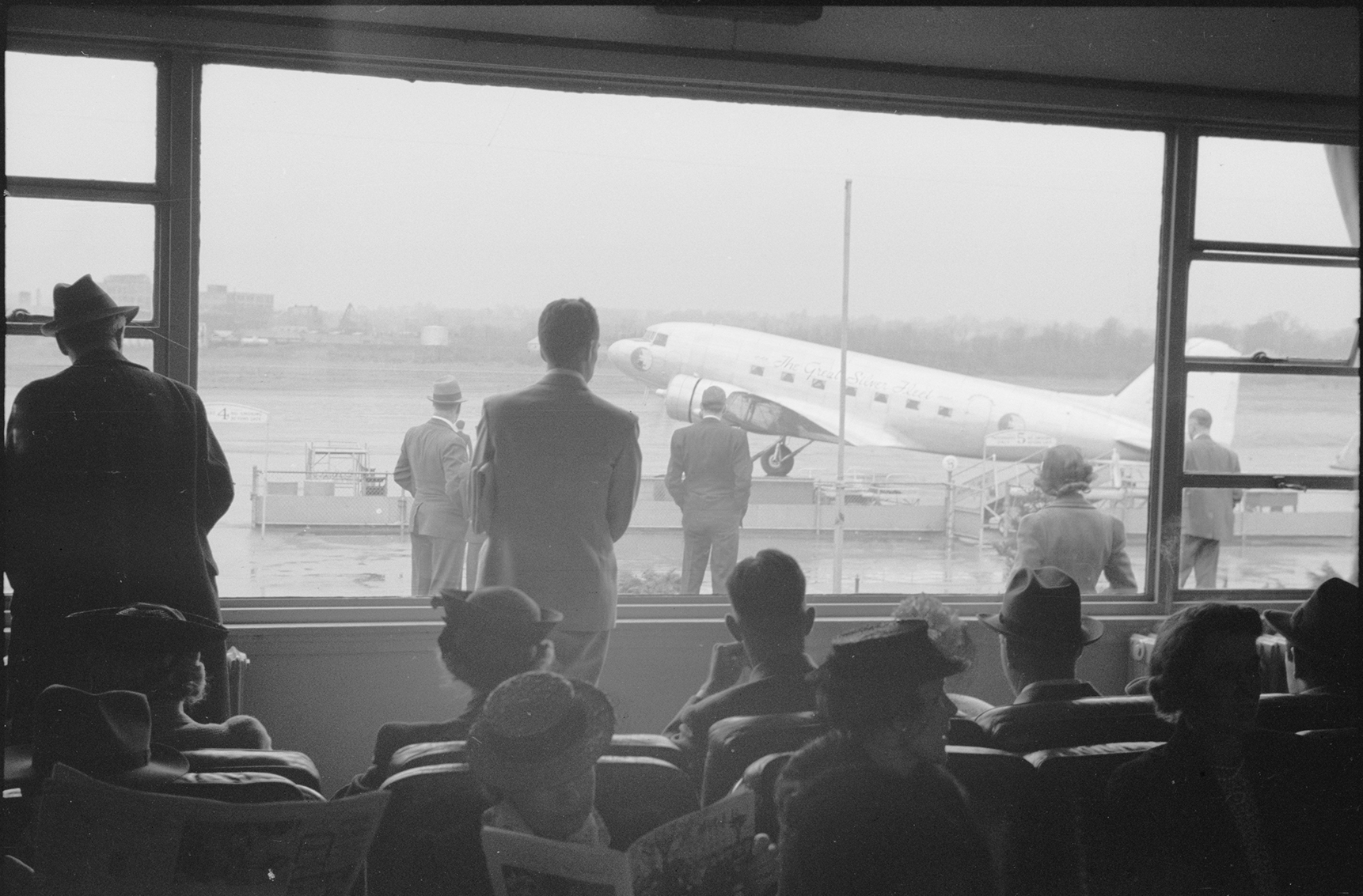 a group of travelers wait in an airport gate and watch out the windows to the runway