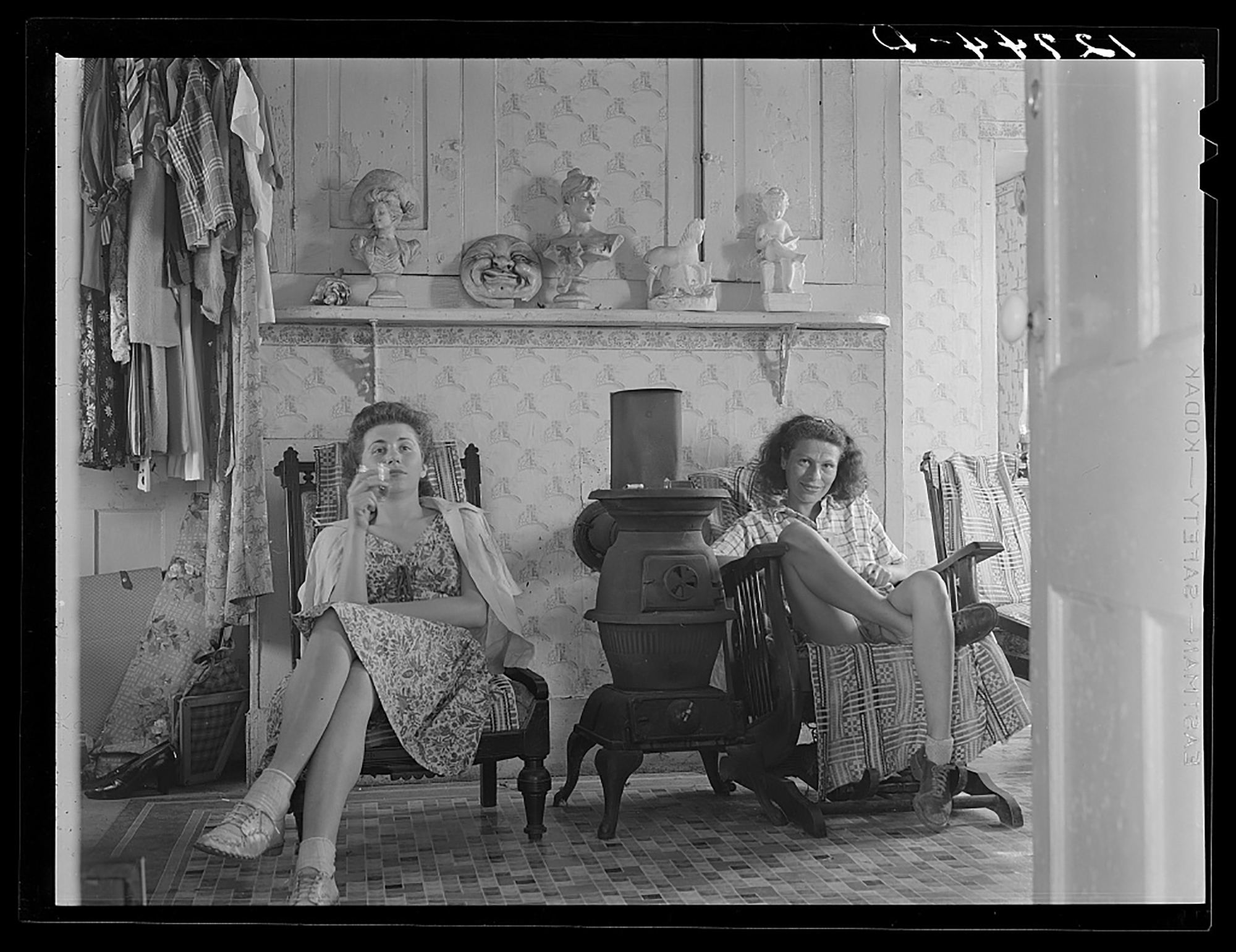 two women sit inside a home in the 1940s