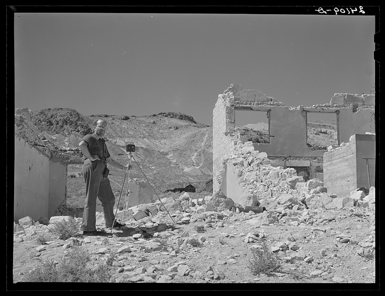 a man takes a photo next to ruins