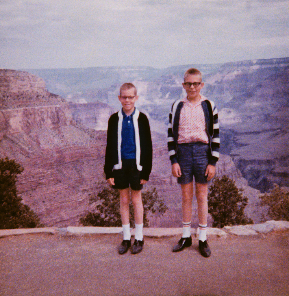 two boys pose in front of the grand canyon