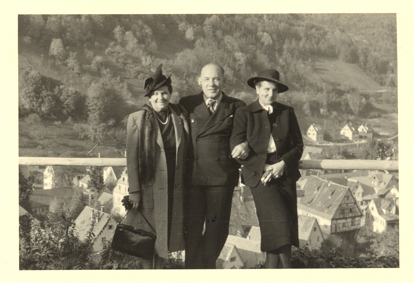 a man and two women pose in front of a european village