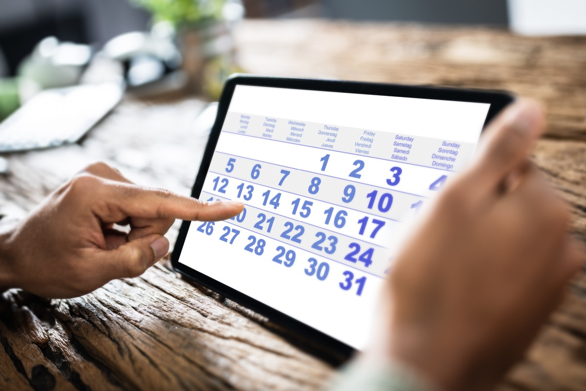 man using digital calendar on iPad.