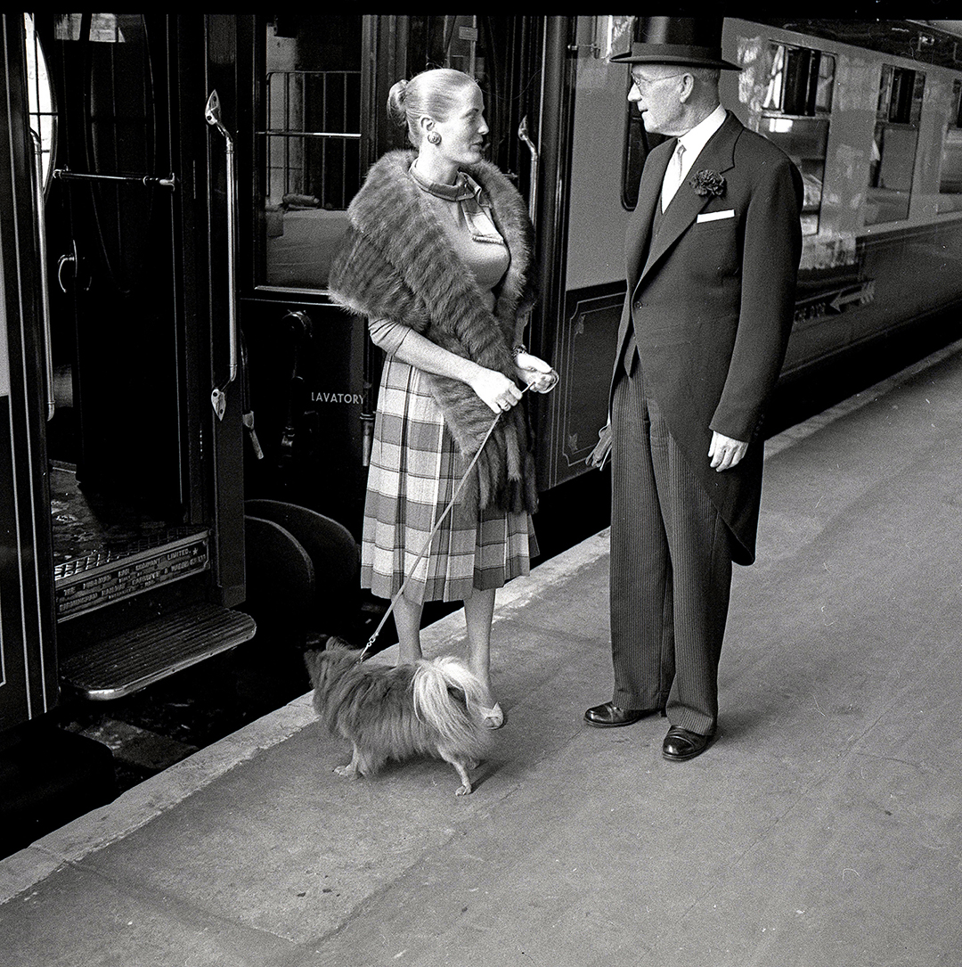 a train maitre d' talks to a woman and her dog