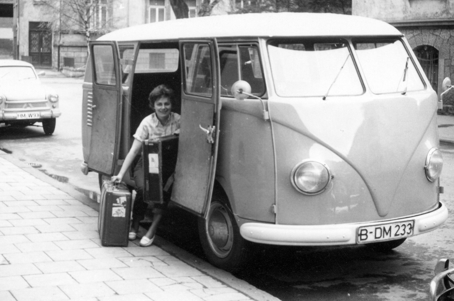 a woman sits in a camper van with two suitcases