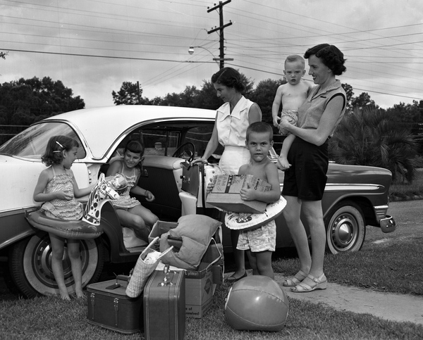 two mothers and four kids get out of a vintage car
