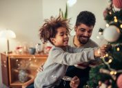 Father and daughter decorating tree