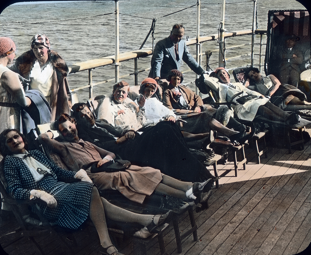 a group sit on a sundeck of a ship in the 1920s