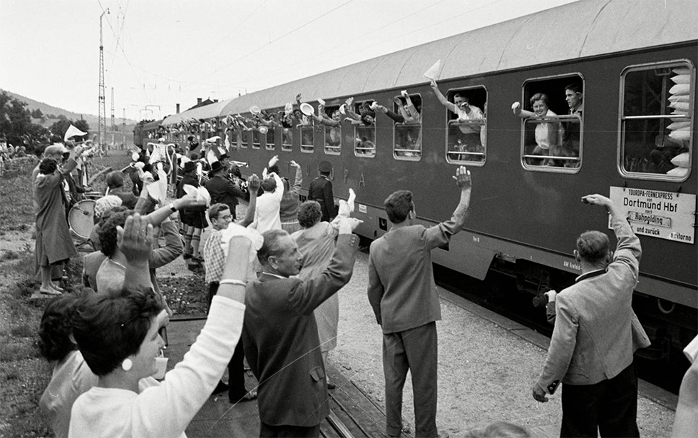 a group of people wave at train passengers