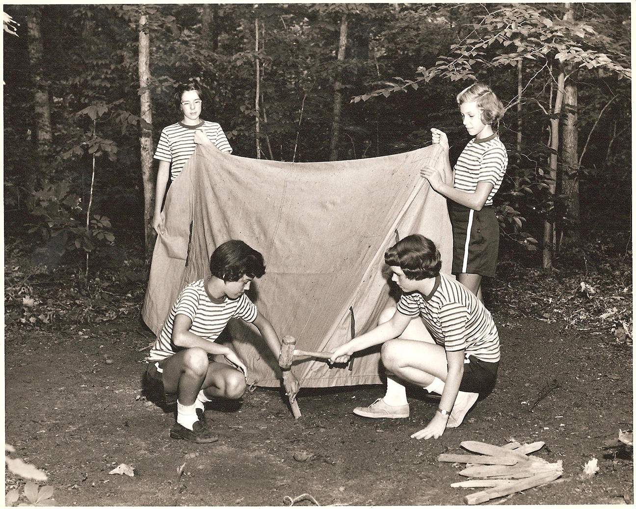 three girls set up a tent in the woods