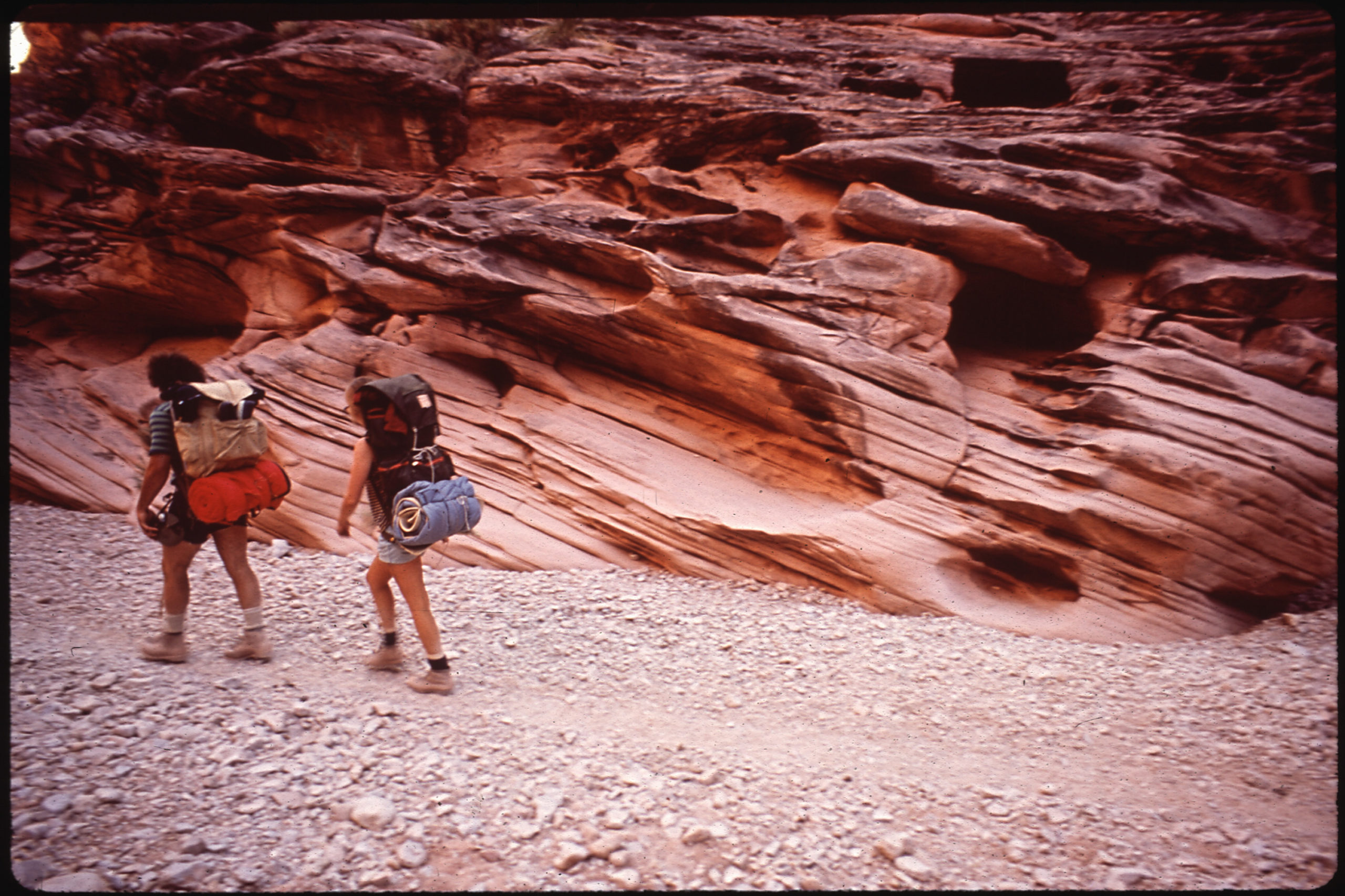 two hikers walk through a canyon