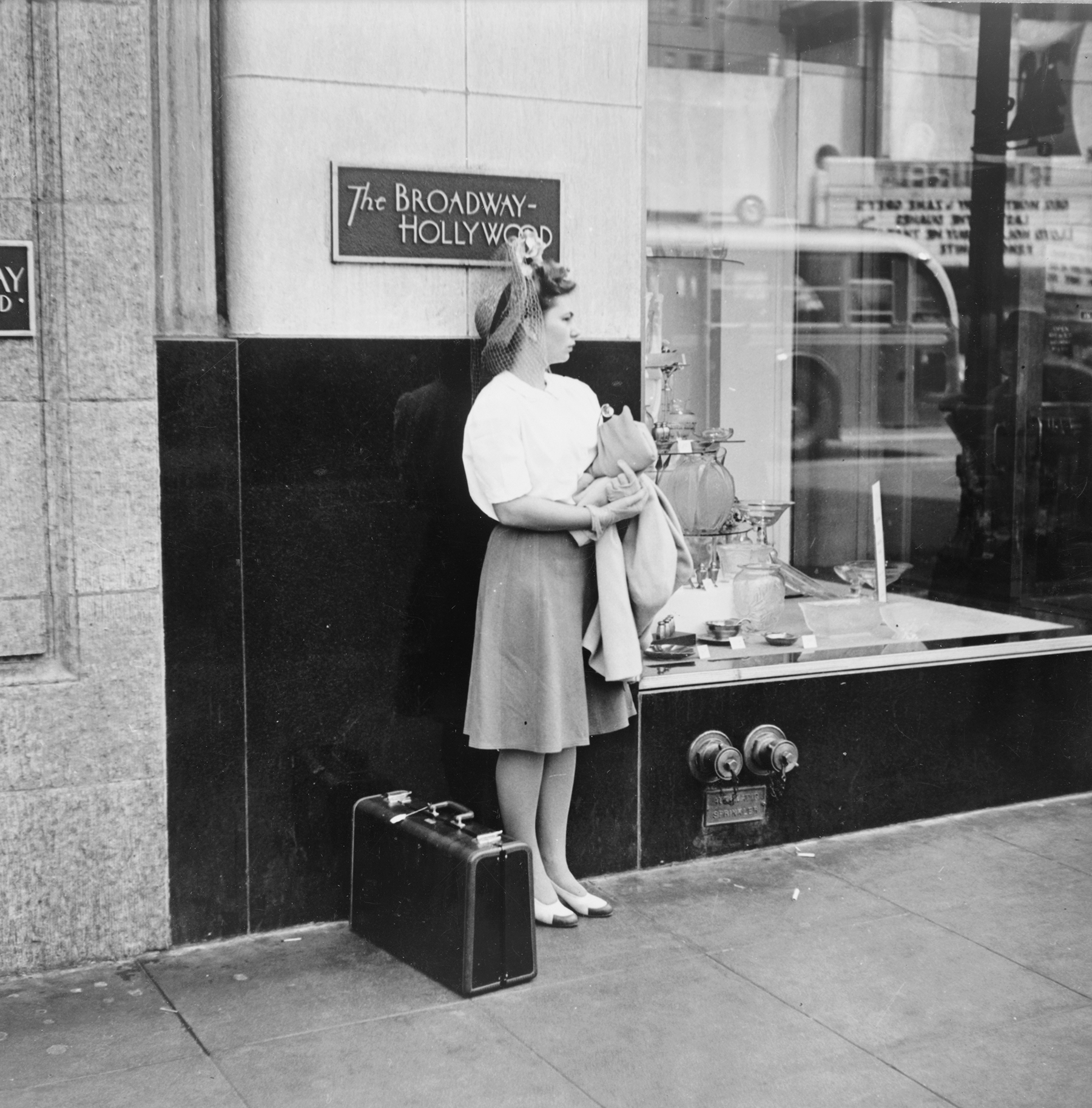 a young woman waits on hollywood boulevard with her suitcase
