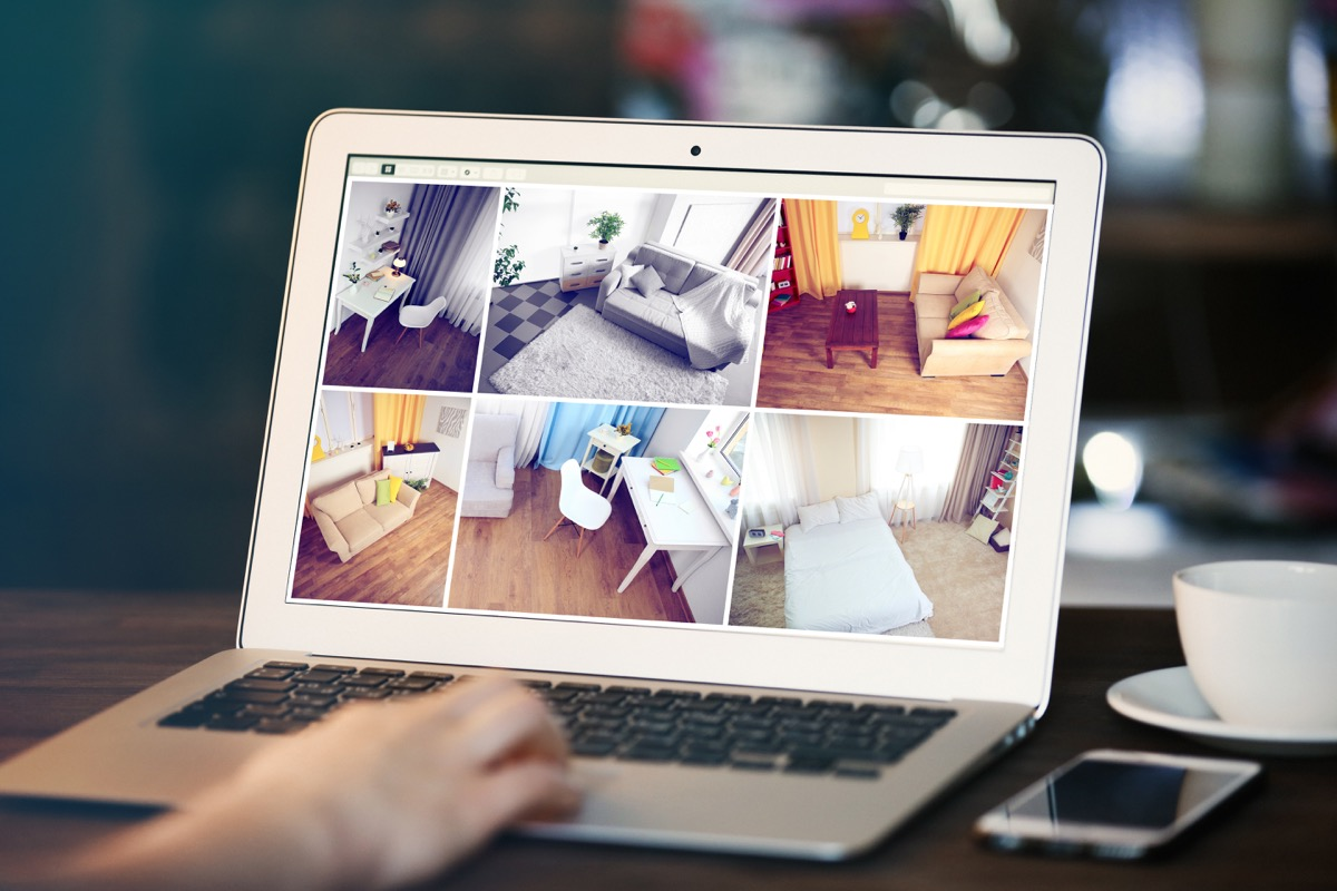 Laptop with security camera monitoring different rooms