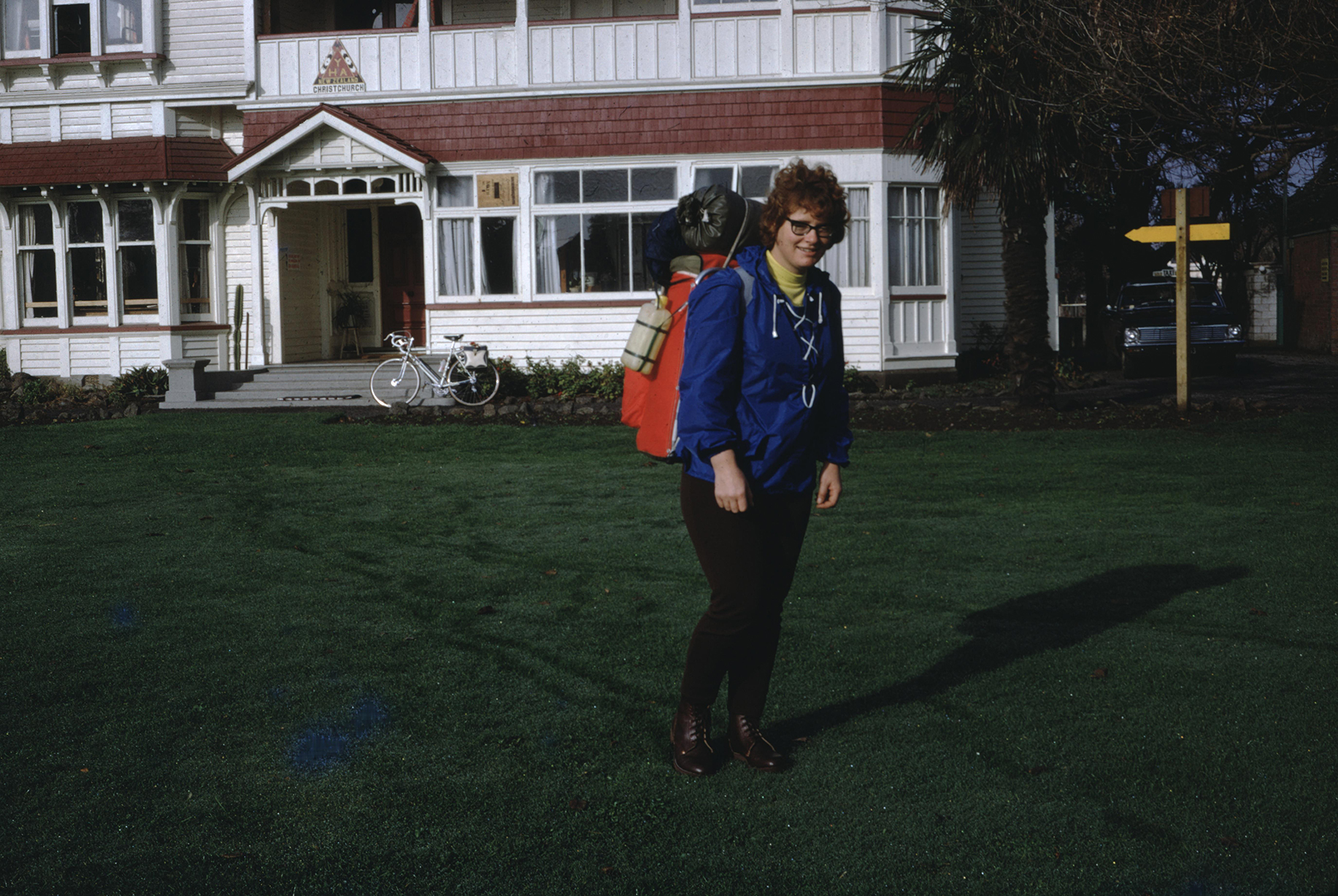 a female backpacker poses in front of a house