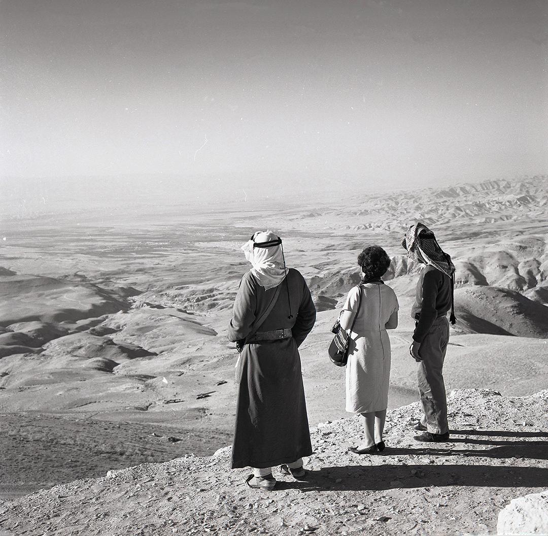 a woman and two men look at a desert in Jordan