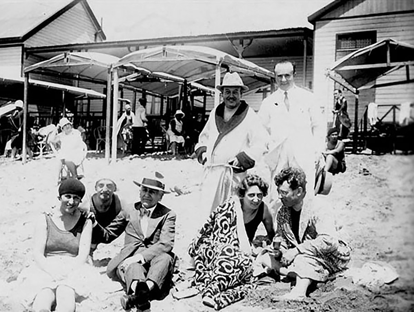 a group of men and women pose on a beach in the 1930s