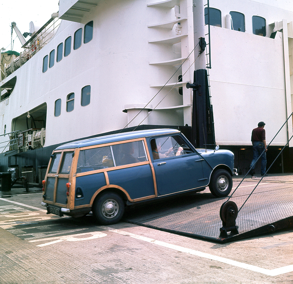 a car drives on a ferry in the 1960s