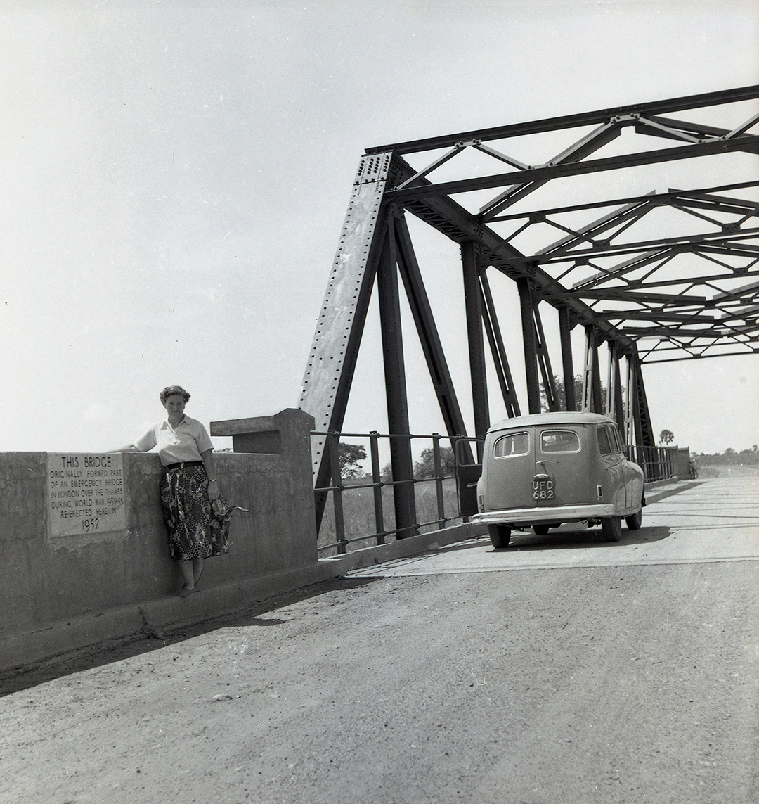 a woman poses in front of a bridge