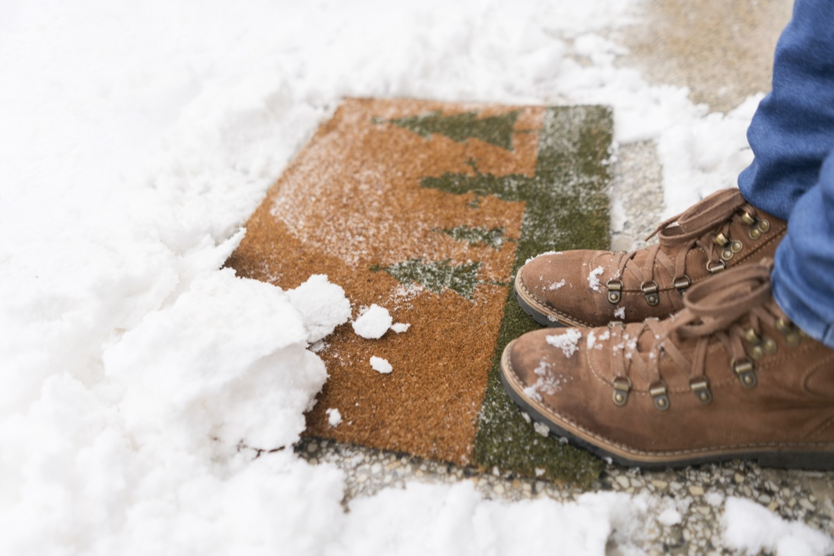 One person standing on a snowy doormat