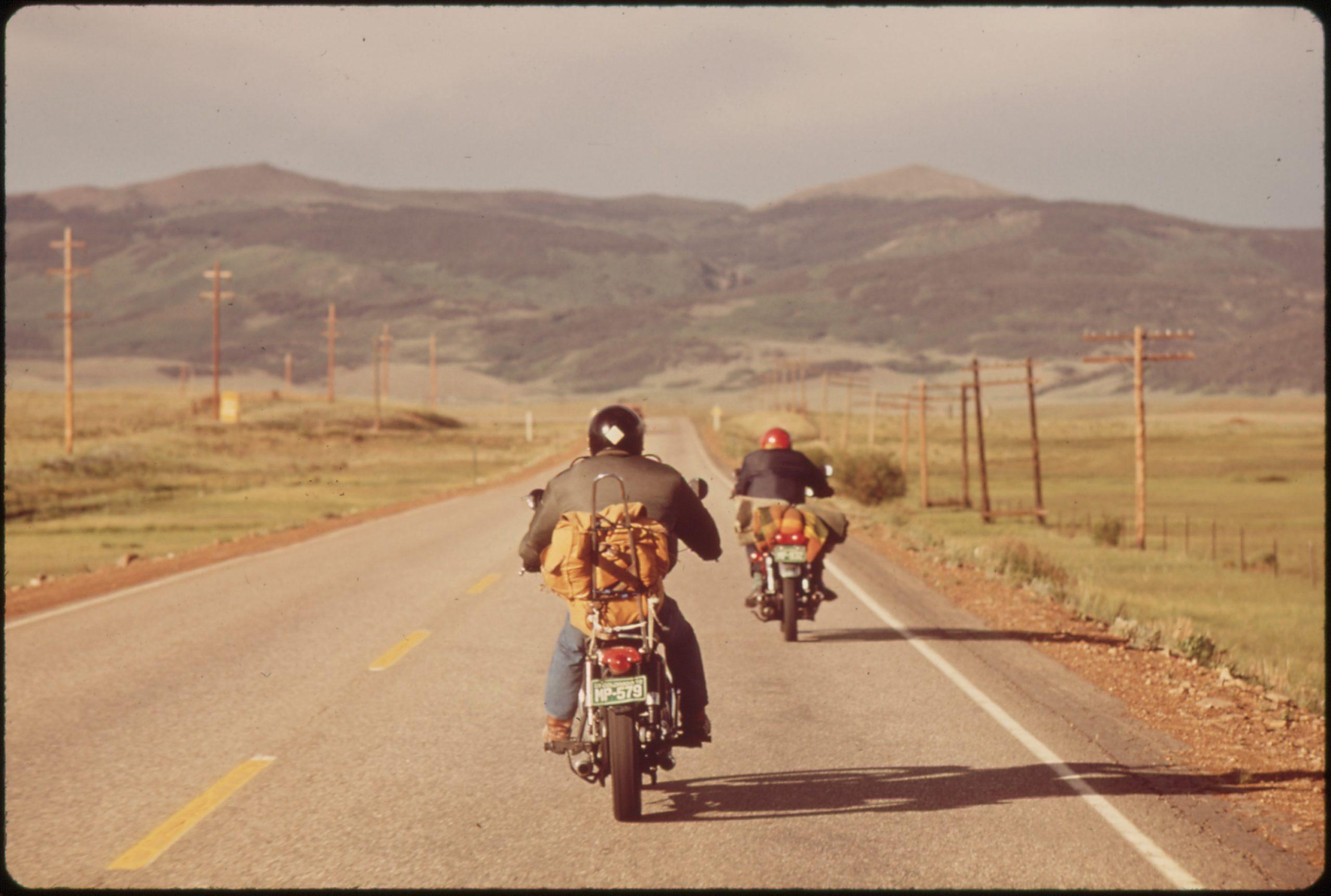 two men ride motorcycles