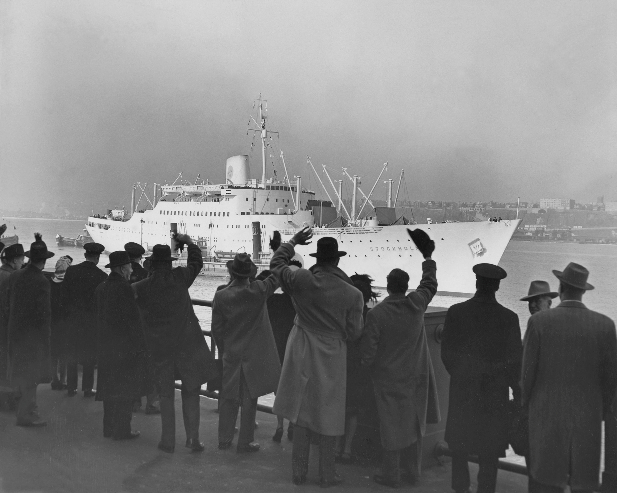 a group of people waves at a cruise ship