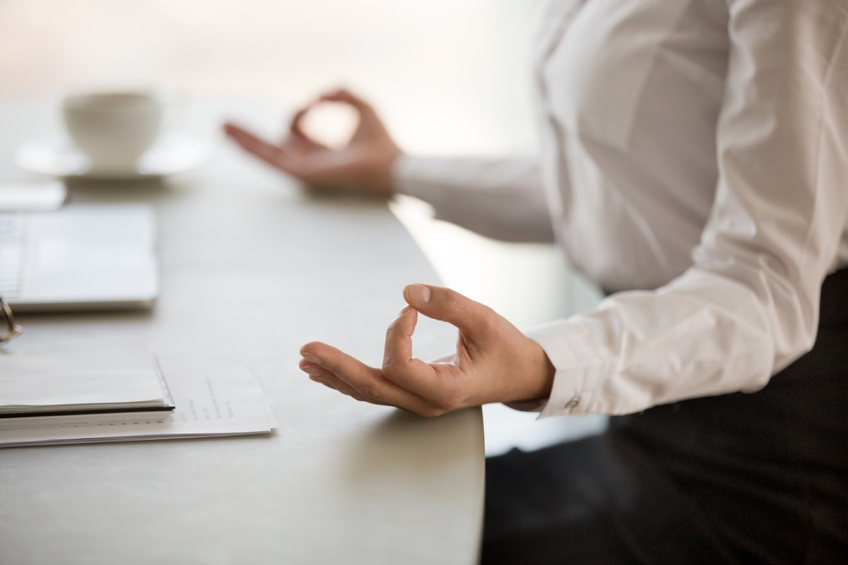Woman taking a break to meditate at work