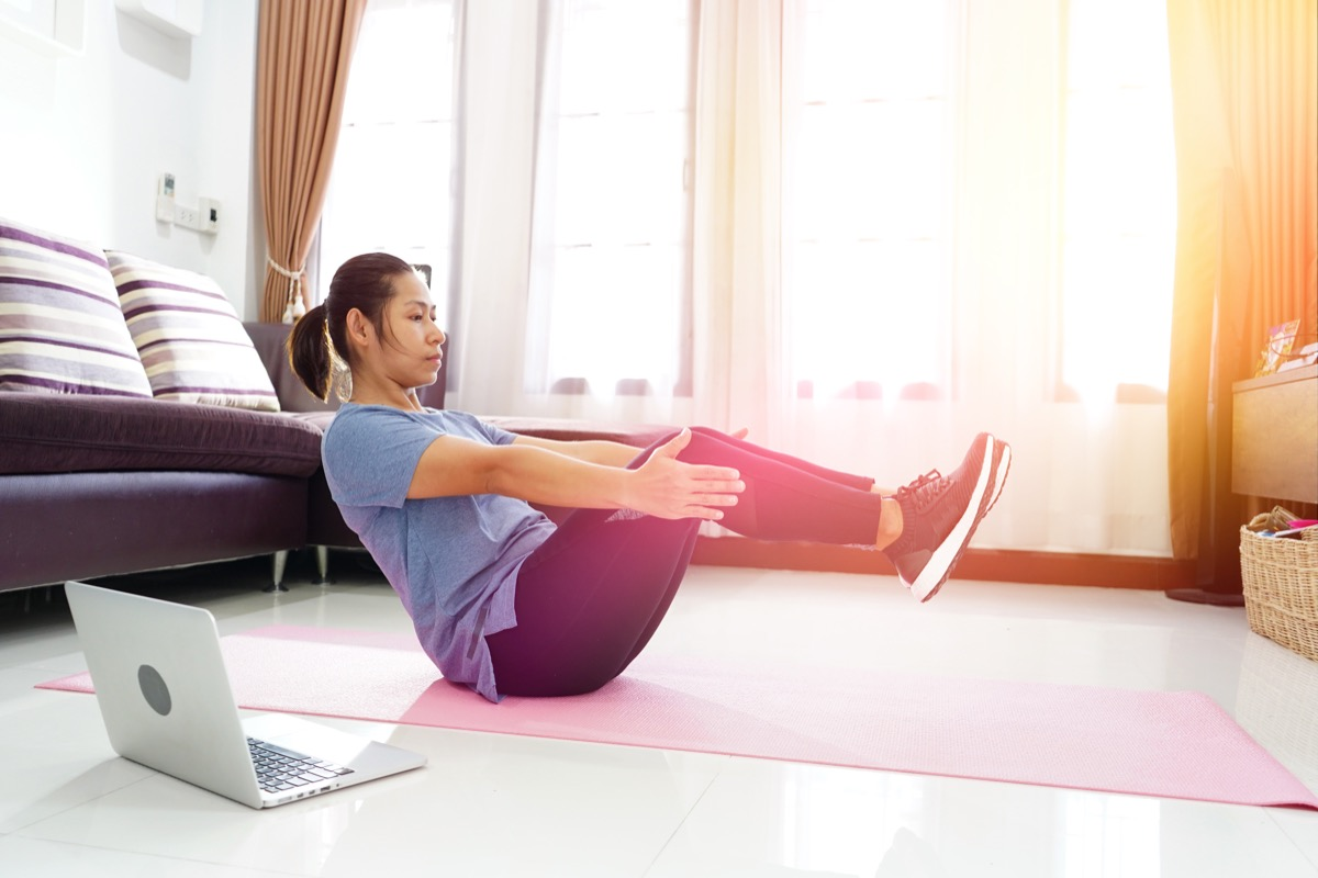 Woman doing an ab exercise workout in the living room